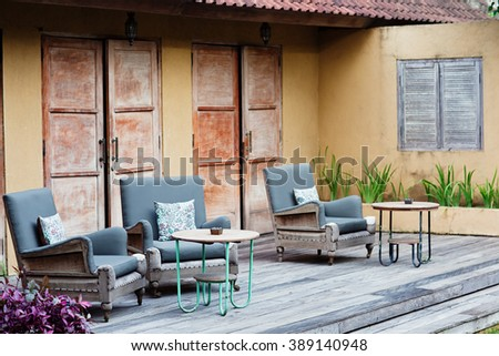 Outdoor patio seating with nice bench chairs at sunset - stock photo