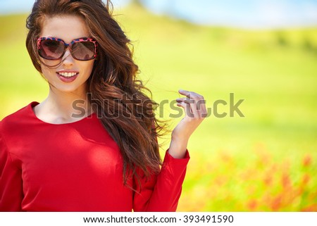 outdoor photo of beautiful sexy girl  in elegant dress posing in summer field of red poppies  - stock photo