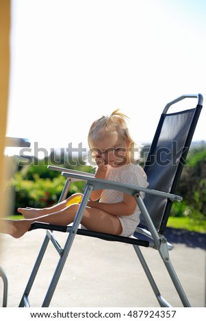 Outdoor photo of cute little girl having sunbath at chair and enjoying her leisure time.