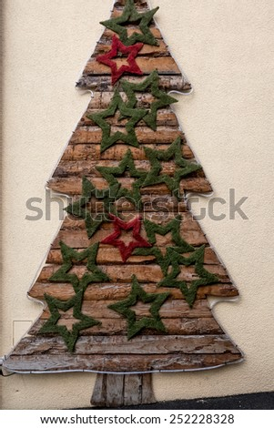 Outdoor photo of decorative Christmas tree on building wall - stock photo
