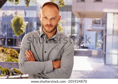 Outdoor photo of handsome young man standing arms crossed, smiling. - stock photo