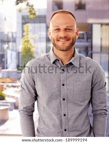 Outdoor photo of happy young man smiling, looking at camera.