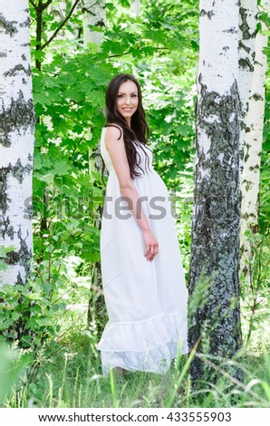 Outdoor photo of pregnant woman near the birch.