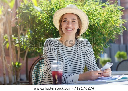 Outdoor photo of pretty European girl dressed casually and trendy as she spends leisure time in cafe outdoors while looking happily at interlocutor, listening with interest and holding mobile phone