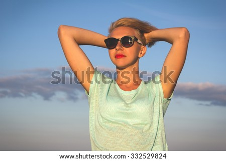 Outdoor photo of sexy beautiful elegant woman with short blonde hair resting on the summer beach next to the blue sea