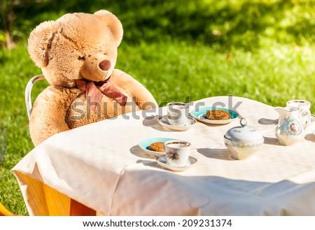 Outdoor photo of teddy bear sitting at yard and having english breakfast - stock photo