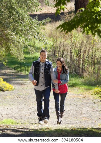Outdoor photo of young couple walking on pathway in nature setting