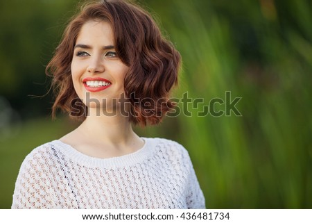 Outdoor photo of young woman. Beautiful tender woman with red hair posing in summer park. - stock photo