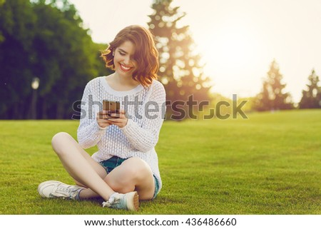 Outdoor photo of young woman sitting on trimmed green grass field. Beautiful tender woman with red hair posing in summer park. - stock photo
