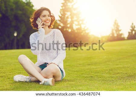 Outdoor photo of young woman sitting on trimmed green grass field with cell phone. Beautiful tender woman with red hair posing in summer park. - stock photo