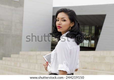 Outdoor photo of  young woman walking carrying books turning head - stock photo