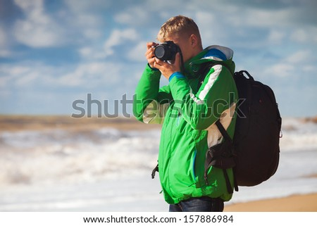 Outdoor photography. Young man with camera makes sea snapshot - stock photo