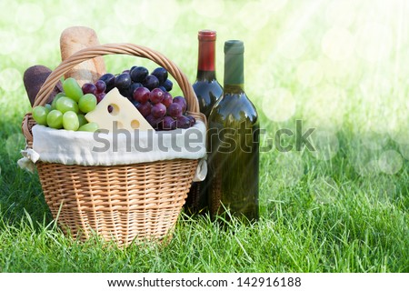 Outdoor picnic basket with bread, cheese and grape and wine bottles on lawn - stock photo