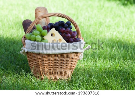 Outdoor picnic basket with bread, cheese and grape on green lawn - stock photo