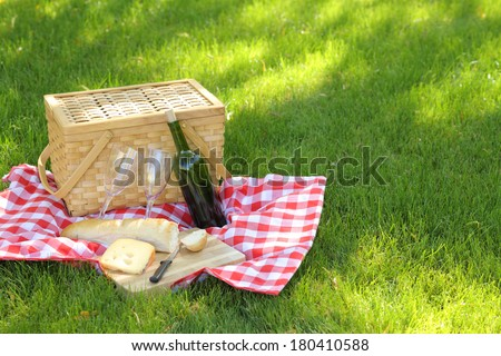 Outdoor picnic, with basket, wine, bread and cheese - stock photo