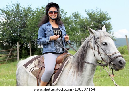 Outdoor picture of a woman on white horse