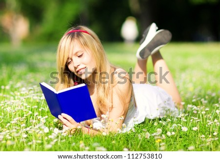 outdoor picture of lovely teenage girl with book - stock photo
