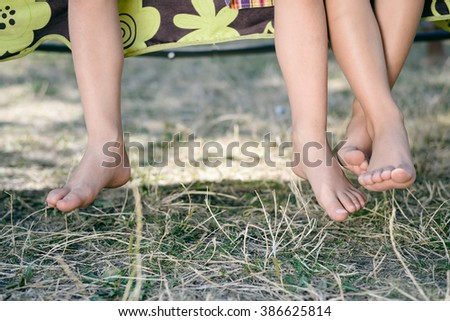 Outdoor picture of two children legs barefoot. Closeup of happy kids sitting on sunny countryside background. - stock photo