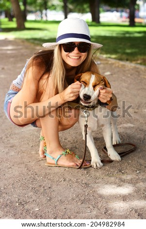 Outdoor portrait. Beautiful smiling woman playing with her dog on green summer park - stock photo