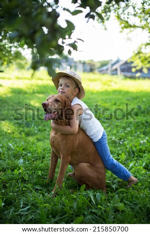 Outdoor portrait: Handsome Young Boy Playing with His Dog at the park - stock photo