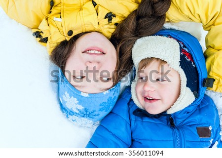 Outdoor portrait Happy mother and baby lying on the snow in winter park and smiling - stock photo