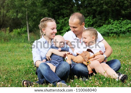 Outdoor portrait of a amazing family sitting on a grass - stock photo