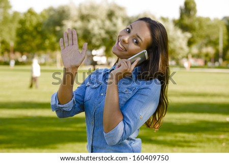 Outdoor portrait of a beautiful African American talking at phone - stock photo