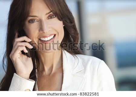 Outdoor portrait of a beautiful happy brunette woman or businesswoman in her thirties talking on her cell phone - stock photo