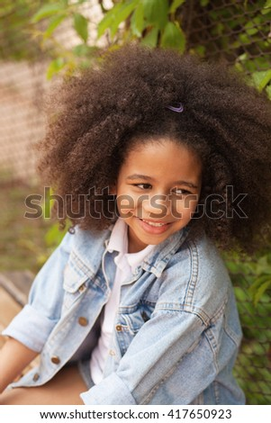 Outdoor portrait of a beautiful little girl wearing jean jacket