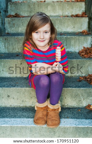 Outdoor portrait of a beautiful little girl with ice cream in a colorful dress