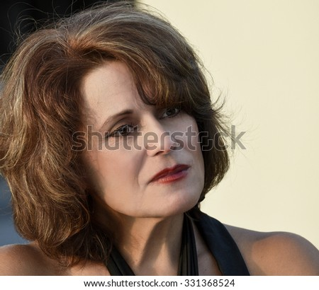 Outdoor Portrait of a Beautiful Mature Woman in the Late Evening Sun   - stock photo