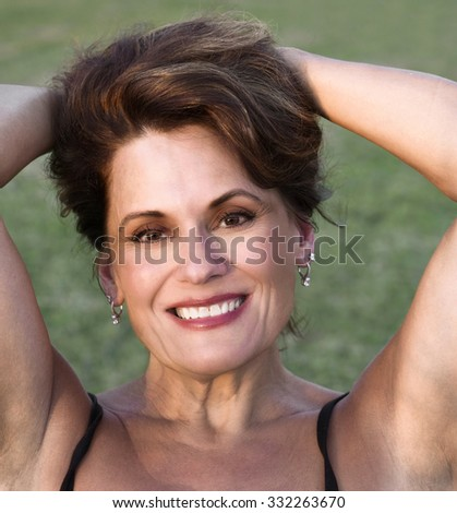 Outdoor Portrait of a Beautiful Mature Woman pulling her hair back in the late evening light - stock photo