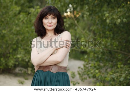 Outdoor portrait of a beautiful middle aged brunette woman in her forties. Lifestyle, lifting make up - stock photo