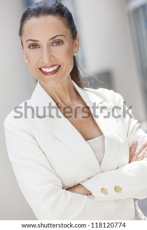 Outdoor portrait of a beautiful smart brunette woman or businesswoman in her thirties wearing a suit - stock photo