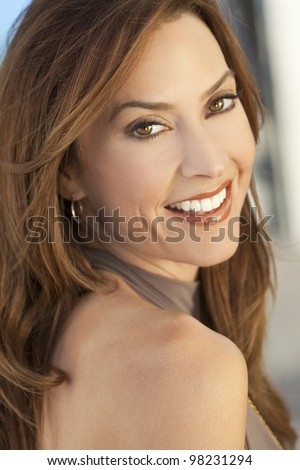 Outdoor portrait of a beautiful smiling young brunette woman in her thirties looking back over her shoulder. - stock photo