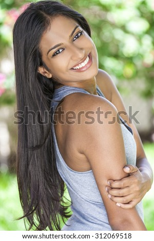 Outdoor portrait of a beautiful sporty Indian Asian young woman or girl outside in summer sunshine with perfect teeth and long hair - stock photo
