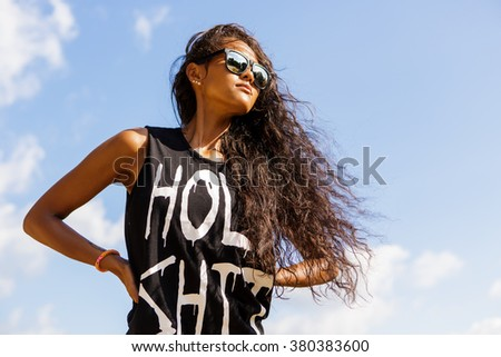 Outdoor portrait of a beautiful teenage black girl with curly hair in dark sunglasses and t-shirt. Lifestyle portrait with blue sky at background. Freedom and happiness. - stock photo
