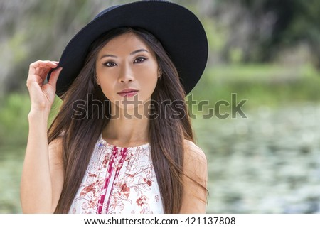 Outdoor portrait of a beautiful thoughtful young Chinese Asian young woman or girl wearing a summer dress and a black hat - stock photo