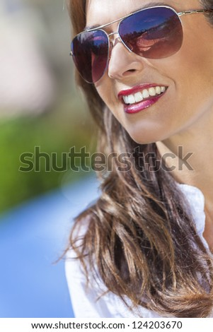 Outdoor portrait of a beautiful young brunette woman in her thirties wearing aviator style sunglasses