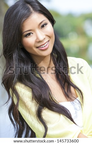Outdoor portrait of a beautiful young Chinese Asian young woman or girl - stock photo