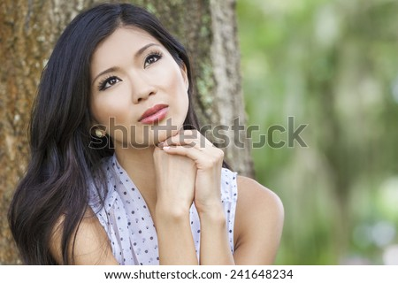 Outdoor portrait of a beautiful young Chinese Asian young woman or girl with natural green background - stock photo