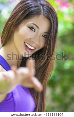 Outdoor portrait of a beautiful young Chinese Asian young woman or girl with perfect teeth, reaching to camera. - stock photo