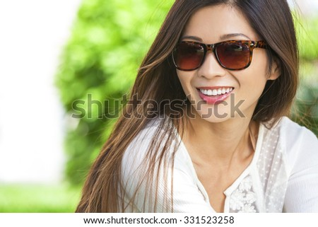 Outdoor portrait of a beautiful young Chinese Asian young woman or girl with perfect teeth wearing sunglasses - stock photo
