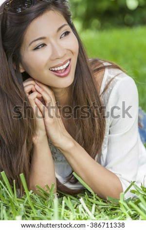 Outdoor portrait of a beautiful young happy smiling Chinese Asian young woman or girl - stock photo