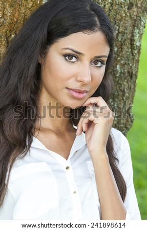 Outdoor portrait of a beautiful young Latina Hispanic girl or young woman leaning against a tree - stock photo
