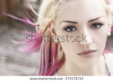 Outdoor portrait of a beautiful young woman or girl with brown eyes, blond and magenta pink hair - stock photo