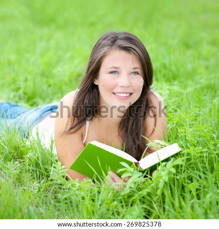 Outdoor portrait of a beautiful young woman reading a book