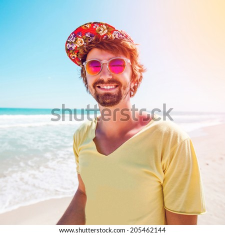 Outdoor portrait of a cheerful guy in a cap and colored glasses resting and having fun on a sunny beach - stock photo