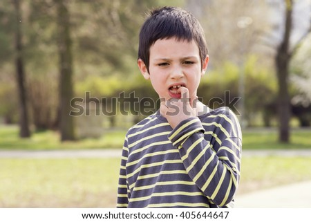 Outdoor portrait of a child boy with a finger in his mouth touching a loose tooth.