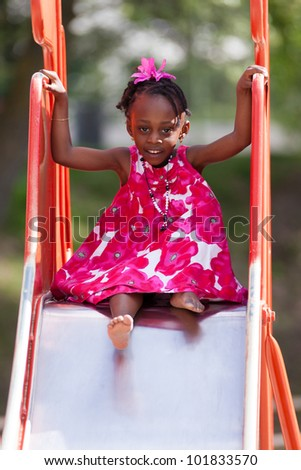 Outdoor Portrait of a cute african american little girl playing at playground - stock photo